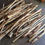 A pile of willow branches, bark removed. Various diameters and lengths.