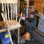 The woodworker is shown holding up a piece of wood while considering whether to incorporate it into the chair.