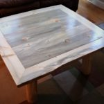 Coffee table from blue-stained pine; robust live-edge frame and log legs.