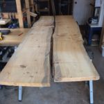 2 blue-stained pine slabs, over 8 feet long sit side by side in the woodshop.