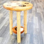 Side table with inlaid bike cogs. Reclaimed barnwood for the tabletop and bottom shelf; hand-peeled lodgepole pine legs. I inlay the cogs by pencil tracing around them, then free-handing the pattern with a router, finally coating the whole surface in clear epoxy resin.