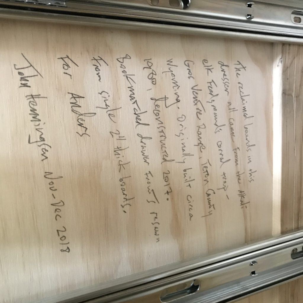 The inside surface of a dresser, showing a paragraph, hand-written in pencil, explaining where the reclaimed wood came from.